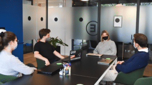 Workers meet during the pandemic to discuss marketing images. Photo by: Cherrydeck (Unsplash)