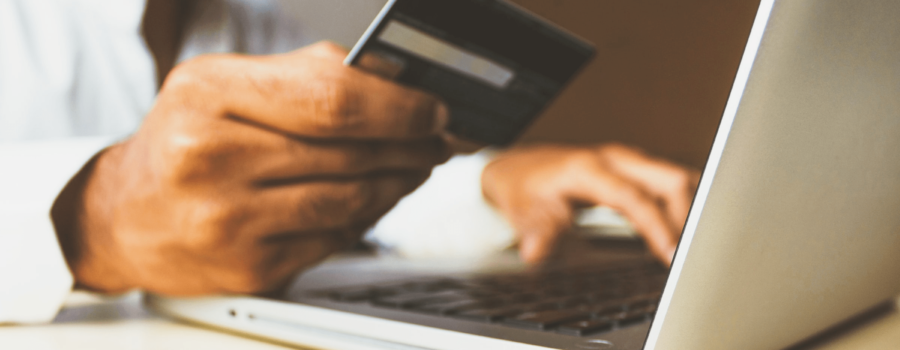 A man makes an e-commerce purchase using a credit card. Marketing Nice Guys has 6 fixes for improving e-commerce sites. Credit: Rupixen.com