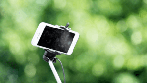 A video marketer uses a selfie stick to create marketing content.