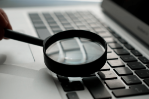 An image of a magnifying glass on a computer, a metaphor for search and search engine optimization (SEO). Credit: Agence Olloweb.