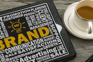 The image depicts a graphic and word cloud around branding. Brand identity is a hugely misunderstood aspect of a small business success.
