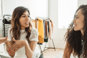 Employees for a small business clothing retailer discuss marketing needs.